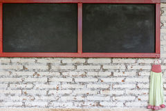 White brick wall with empty black board Royalty Free Stock Photos