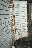 White brick wall and old rusty metal blinds Royalty Free Stock Photography