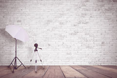 White brick wall in a photo studio. An umbrella for illumination and a tripod for a camera. Empty copy space Stock Photos