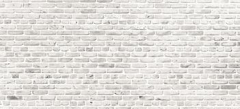 White brick wall. Simple grungy white brick wall with light gray shades pattern surface texture background in wide panorama format.  royalty free stock photography