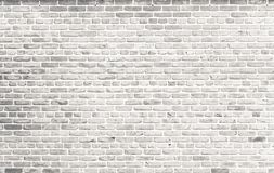 White brick wall. Simple grungy white brick wall with light gray shades pattern surface texture background in wide format.  royalty free stock photography
