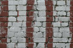 White brick wall with stripes of red paint. Old brick wall with painted red. Bricks background, pattern, texture. Grunge masonry f. Acade of building royalty free stock photography