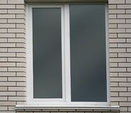 White brick wall and window. Plastic window in white brick wall from outside Stock Images