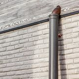White brick wall with wooden frontal board and copper pipe during construction stock photo