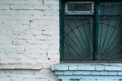 White brick wall. Wooden green window with iron bars stock photos