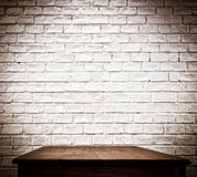 White brick wall and wooden table.  royalty free stock image