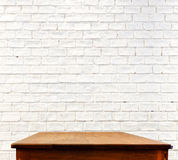 White brick wall and wooden table.  stock images