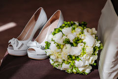 White bridal bouquet and white shoes on the brown chair Stock Photography
