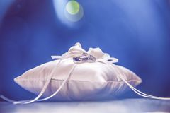 White Bridal Pillow and White Gold Wedding Rings with Light Flare on Dark Leather Sofa. royalty free stock image