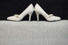 White bridal shoes on black backgound. White bridal showes on textile black backgound. Indoor shot with artificial light Royalty Free Stock Photography