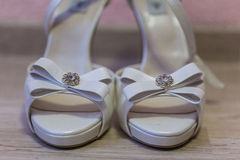White bridal shoes with gems. Indoor shot with artificial light Royalty Free Stock Photos