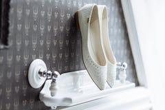 White bridal shoes with luxury stones. White bride luxury shoes without a heel with stones on a white shelf stock photos