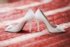 White bridal wedding shoes on red sofa. Marriage concept Stock Image