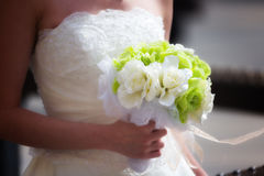 White bride and bouquet. White dressed Asian bride holding a green and white fake flowers bouquet Stock Photo