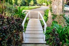 White bridge across walkway sylvan. In garden Royalty Free Stock Image