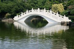 White bridge in an Asian garden. White bridge with reflection in an Asian garden Stock Image