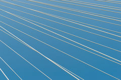 White bridge cable stays in diagonal pattern across blue backgro Royalty Free Stock Photography
