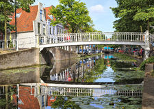 White bridge in Delft, Netherlands. White bridge and small houses reflecting in smooth water of canal in Delft, Netherlands royalty free stock images