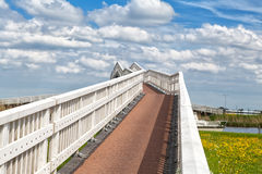 White bridge over blue sky with beautiful clouds. White bridge for bicycles over blue sky with beautiful clouds, Alkmaar Stock Photo
