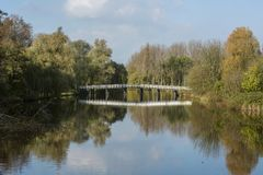 White bridge over the water in the sunny autumn day. With yellow trees around it Royalty Free Stock Photos