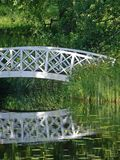 White bridge in park. A white bridge in a park over water with a reflection stock photos