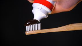 White bristles of the toothbrush with fresh black toothpaste. Squeezing toothpaste from a tube onto a wooden toothbrush. stock footage