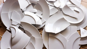 White broken plates on a wooden floor. Many white broken plates on a wooden floor royalty free stock photos