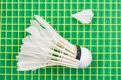 White broken shuttlecock on yellow racket net Royalty Free Stock Photography