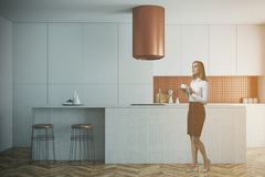 White and bronze kitchen, white countertops toned. White and bronze wall kitchen interior with a wooden floor and white countertops. A woman. 3d rendering mock Stock Photos