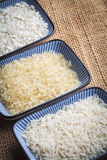 White,brow and basmati rice. White, basmati and brown rice, typical different rice, in a porcelain bowl on jute Royalty Free Stock Image