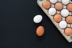 White and brown chicken eggs on black background Royalty Free Stock Photography