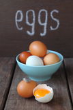 White and brown chicken eggs. On a brown table royalty free stock photo