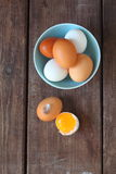 White and brown chicken eggs. On a brown table royalty free stock photography