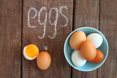 White and brown chicken eggs. On a brown table stock images