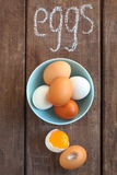 White and brown chicken eggs. On a brown table stock photography