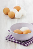 White and brown eggs. In a lilac ceramic cup Stock Photo