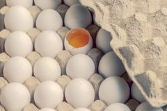White and brown eggs in carton with broken egg stock photo