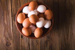 White and brown eggs in a ceramic bowl on a wooden background. Rustic Style. Eggs.  Easter photo concept. Royalty Free Stock Image