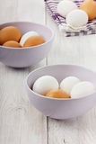 White and brown eggs in a lilac ceramic cup. On a wooden surface Stock Photography