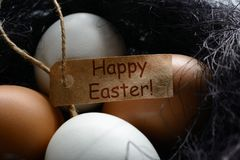 White and brown eggs a nest from sisal with greeting label Happy Easter stock photo