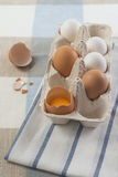 White and brown eggs in paper holder. One broken Stock Images