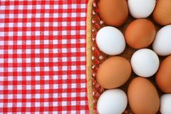 White and brown eggs on a red-and-white tablecloth royalty free stock photography
