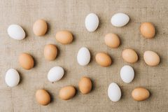 White and brown eggs scatterd. On sackcloth royalty free stock image