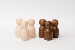 White and brown figures. Three white and three brown figures, seperated in two groups royalty free stock photography