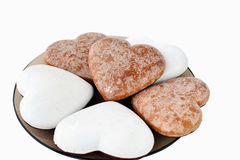 White and brown ginderbread hearts isolated. Heart-shaped gingerbread cookies with sugar icing on a plate, isolated on white background royalty free stock images