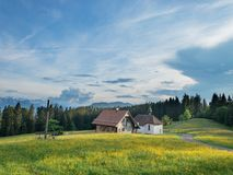 White and Brown House on a Green Field Under Blue Sky stock images