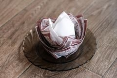 White-brown napkin in the form of a rosette on a wooden background.  stock photos