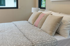 White and brown pillows on bed. Modern bedroom with white and brown pillows on bed royalty free stock photos