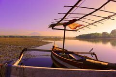 White and Brown Rowboat on Calm Body of Water during Sunset Stock Image