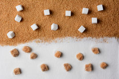 White and Brown Sugar Contrast. White sugar cubes on raw brown turbinado granules and raw brown sugar lumps on white granulated sugar royalty free stock photos